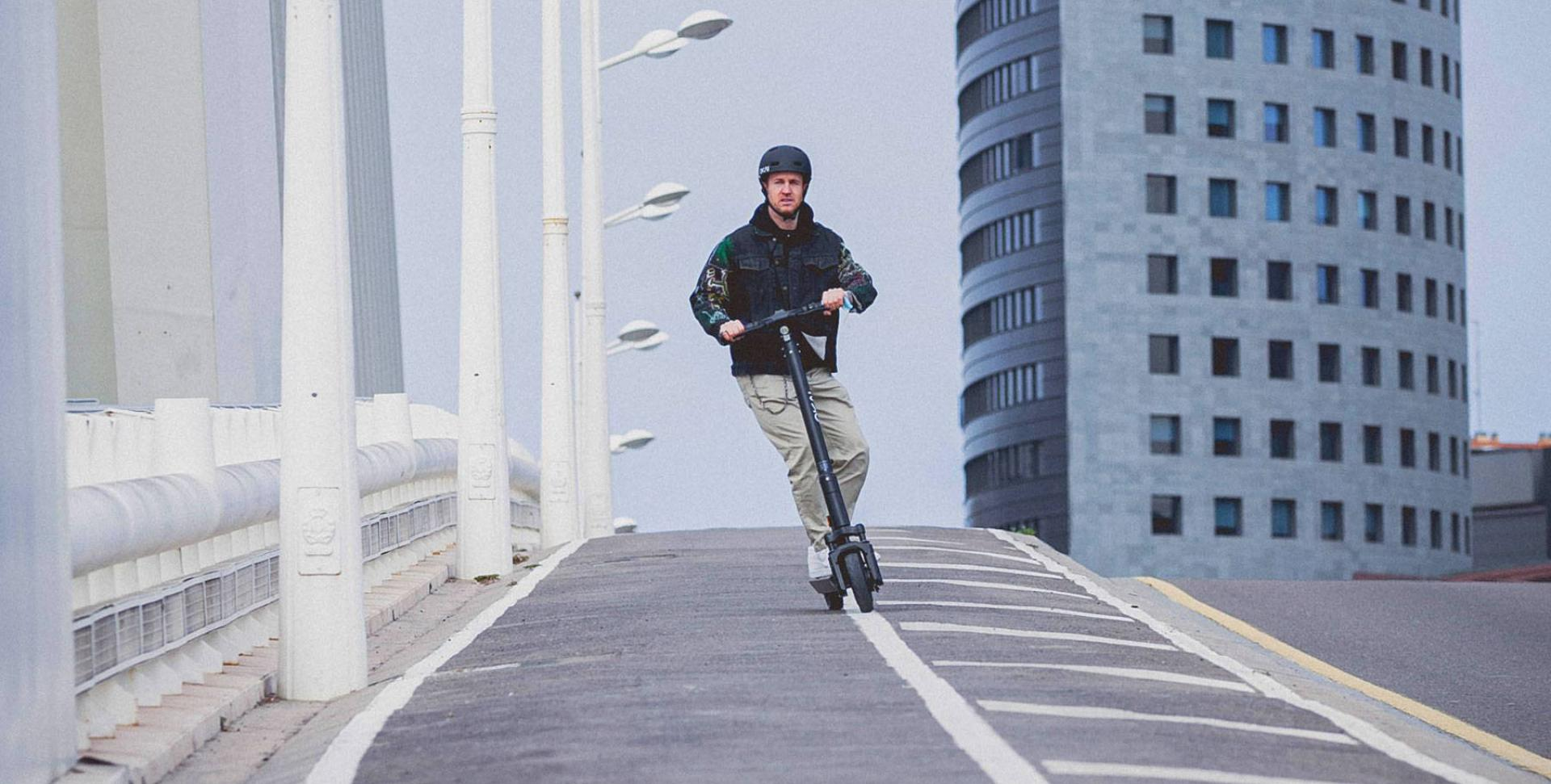 Okai-es200-escooter-man-riding-bridge-city.jpeg